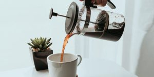 pouring coffee in a cup from a french press