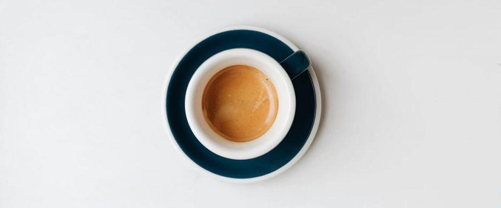 espresso in a white ceramic cup on a blue saucer
