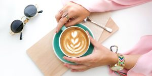 holding a cup of latte with latte art and glasses onthe side
