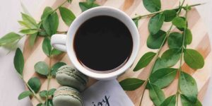 coffee in a ceramic cup with macarons and leaves