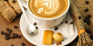 a cup of latte on a saucer with a teaspoon, coffee beans, and small cookies