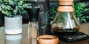 a manual coffee grinder, a wooden saucer with coffee beans and a Chemex pour over pot