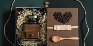 a manual coffee grinder in a box with a wooden spoon and coffee beans