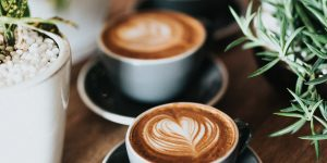 two cups of latte with latte art on saucers