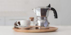 a moka pot with a ceramic cup on a saucer and a teaspoon
