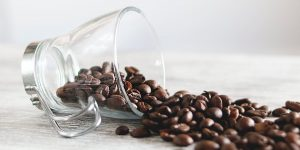coffee beans spilling from a glass