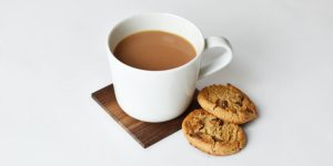 a cup of coffee with 2 chocolate chip cookies