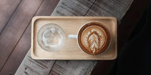 a glass of water with ice and a cup of cappuccino with latte art