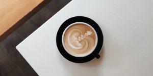 latte in a black ceramic cup on a black ceramic saucer
