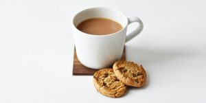 a cup of coffee with cookies on the side
