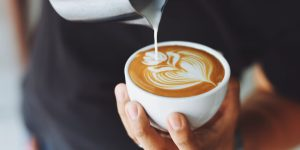 holding a cup of latte while pouring milk