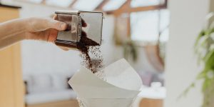 pouring ground coffee into a paper coffee filter