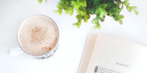 a cup of coffee with a book on the side