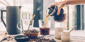 pouring coffee from a Chemex coffee maker into a mug