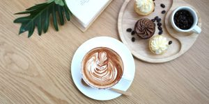 a cup of cappuccino with cupcakes and coffee beans on the side
