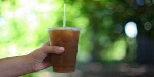 holding a plastic cup of iced coffee