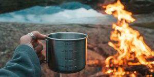 holding a cup in front of a campfire