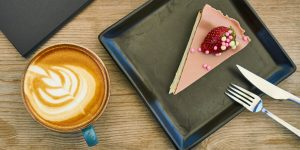 a cup of cappuccino and a slice of cake with a strawberry on top