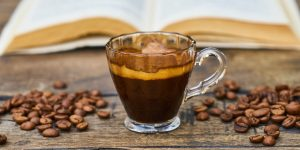 a cup of espresso with coffee beans on the side and a book