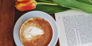 a cup of cappuccino on a saucer with a book and a tulip