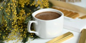 a mug of coffee with flowers and unopened candy bars