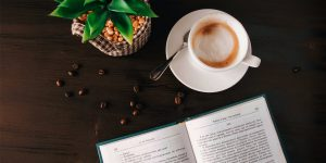 a cup of latte in a saucer with teaspoon, a book, coffee beans and a plant pot