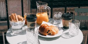 cinnamon buns, coffee cups, glasses of water, a pitcher of iced beverage