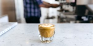 a glass of latte with latte art on a slab