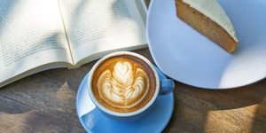 a cup of cappuccino with a slice of cake on a plate, and an open book