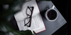 Coffee, an open book and a reading glasses on a table