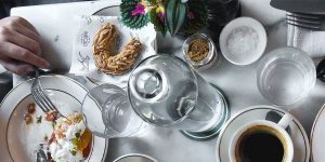 Eating a meal on a dining table with coffee, water and bread
