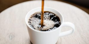 Pouring freshly brewed coffee on a white mug