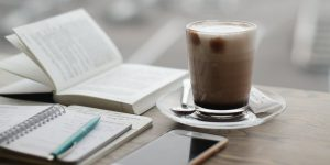 Coffee with notebook, pen, book and phone