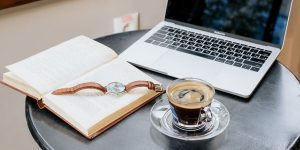 Coffee, laptop, watch and book on a table