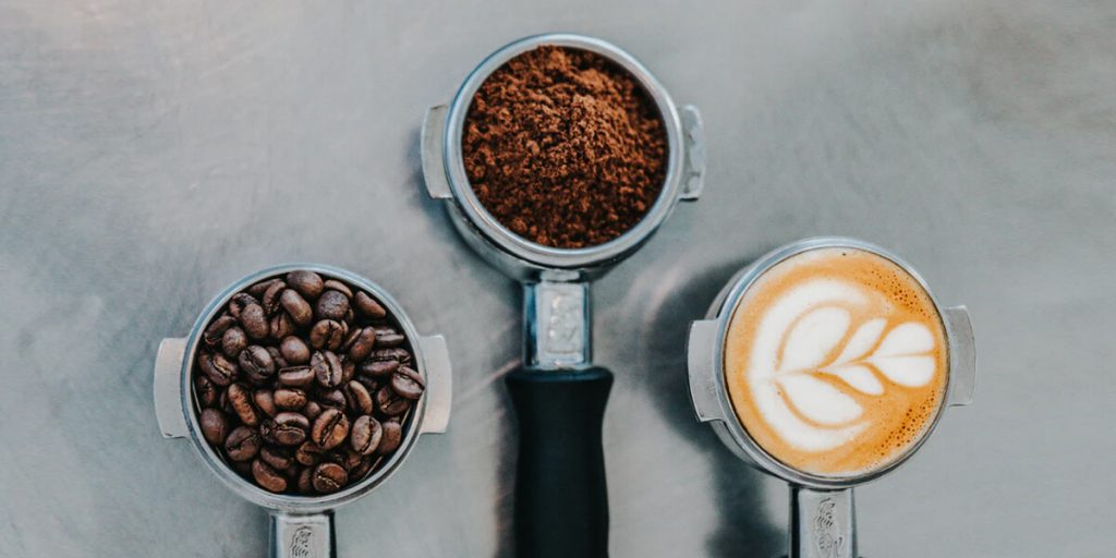 coffee beans, coffee grounds, and latte in portafilters