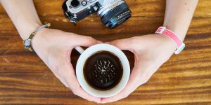 holding a cup of espresso and a camera
