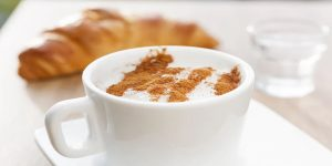 cappuccino with cocoa powder topping and croissant