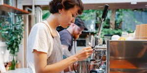 A female barista steaming the milk