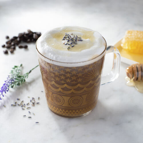 cup of honey lavender latte with dried lavender on top