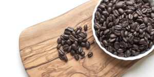 black coffee beans in a white ceramic mug on brown wooden chopping board
