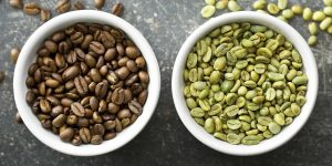 black coffee beans and green coffee beans in a white ceramic small bowl