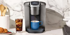 Coffee maker with a blue cup with coffee in it