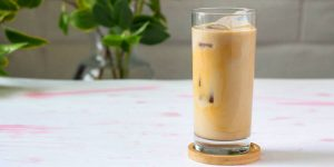 Glass of pale tan coffee milk tea with ice cubes