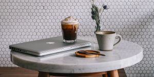 A coffee, laptop, mug and a spoon on a table
