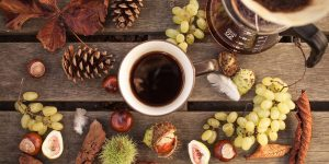 A cup of black coffee surrounds with fruits