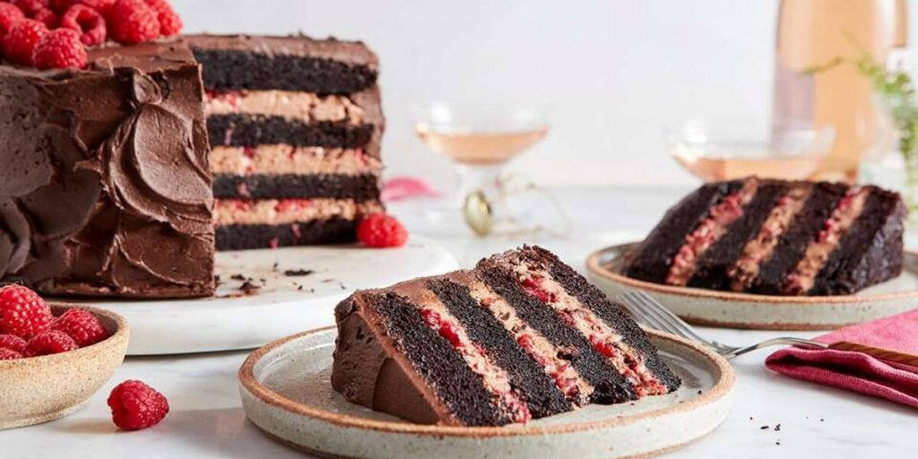 A yummy strawberry covered with chocolate layer cake