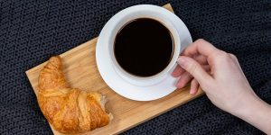 Black coffee on a tray with a croissant on the side