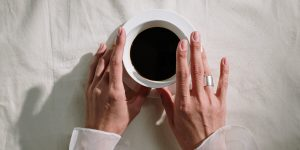 A woman touching the white cup with a black coffee
