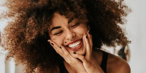 Curly haired woman with a brightest smile