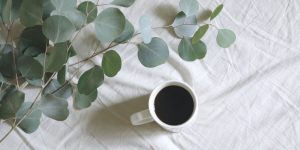 Black coffee on a white cup with a leaves as a background